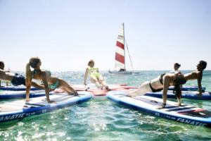 Eine SUP-Yoga-Klasse auf dem Wasser, während Sie eine Yoga-Übung ausführen.